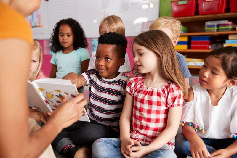 Grupp av grundskolaelever som sitter på golv som lyssnar till lärarinnan Read Story arkivbild