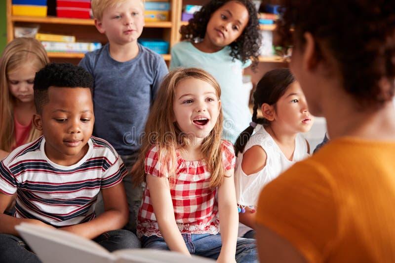 Grupp av grundskolaelever som sitter på golv som lyssnar till lärarinnan Read Story royaltyfri fotografi