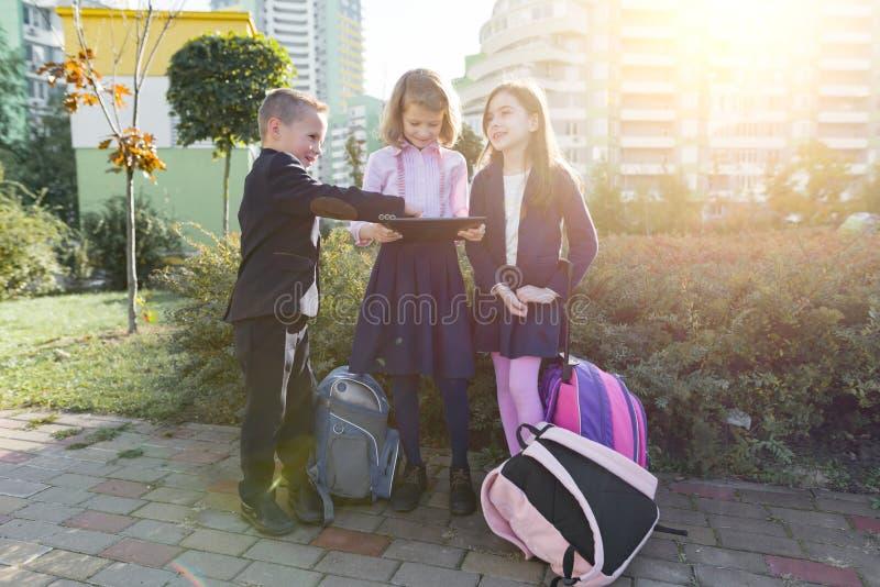 Grupp av grundskolaungar med den digitala minnestavlan Utomhus- bakgrund, barn med skolaryggsäckar som ser minnestavlan, arkivbild