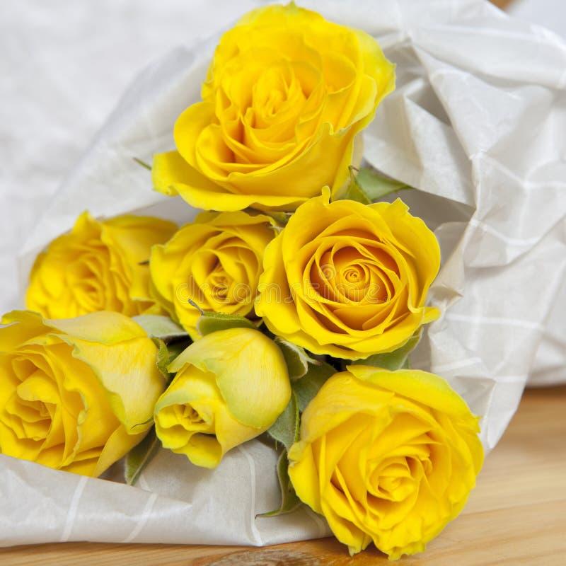 Grupp av gula rosor i blomsterhandlaren som slår in på vit bakgrund arkivbild