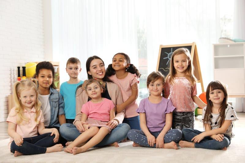 Grupp av gulliga små barn med läraren som sitter på golv arkivbilder