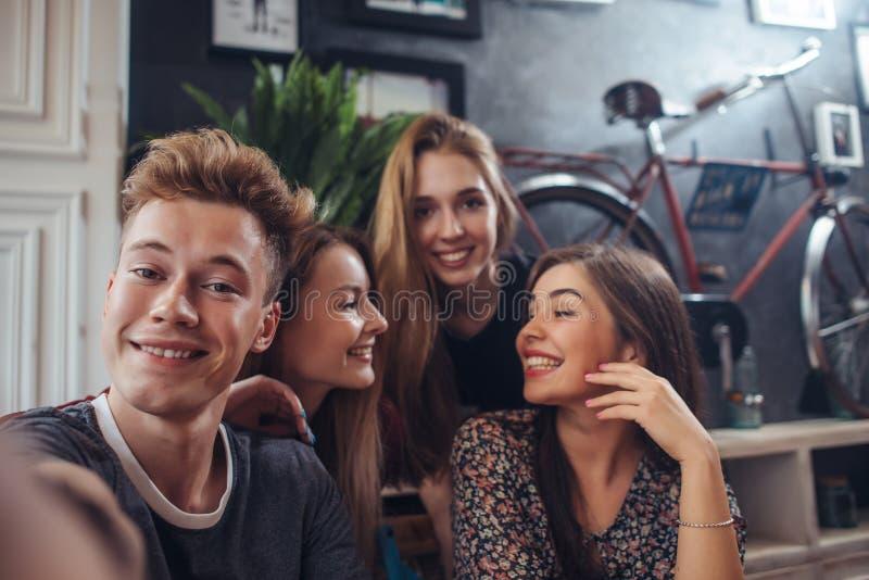 Grupp av gulliga tonåringar som tar selfie med mobiltelefonen, medan sitta i en restaurang med inre i retro stil royaltyfri foto