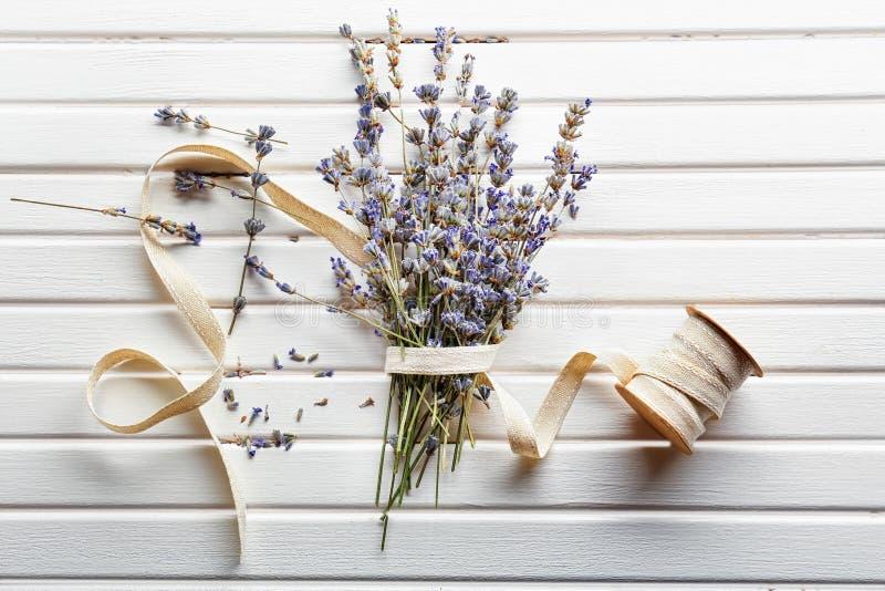 Grupp av härliga blommande det lavendelblommor och bandet på vit träbakgrund arkivfoton