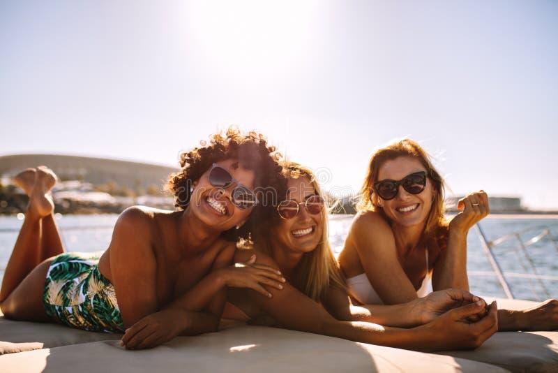 Grupp av härliga kvinnor som kopplar av på ett yachtdäck royaltyfri fotografi