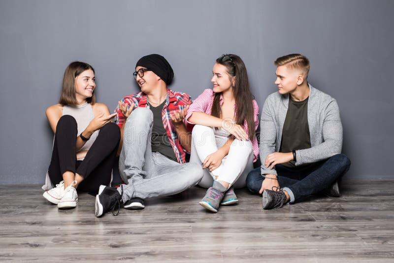 Grupp av härliga studenter i tillfällig kläder genom att använda grejer, tala och le, medan sitta tillsammans på golvet royaltyfria bilder