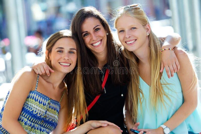 Grupp av härliga unga flickor i gatan isolerar blonda blåa dagögon för påsar shopping som tar white fotografering för bildbyråer