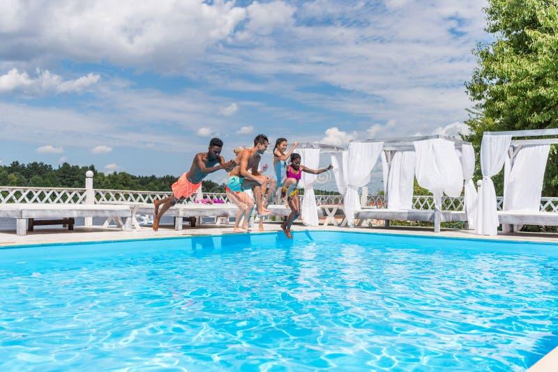 Grupp av härligt ungt multietniskt folk som ser lyckligt, medan hoppa in i simningen royaltyfri bild