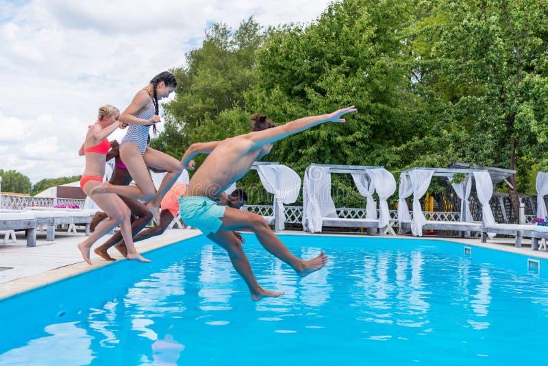 Grupp av härligt ungt multietniskt folk som ser lyckligt, medan hoppa in i simningen arkivbilder