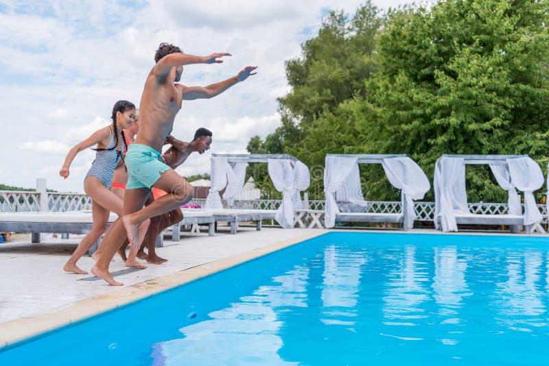 Grupp av härligt ungt multietniskt folk som ser lyckligt, medan hoppa in i simningen royaltyfri fotografi