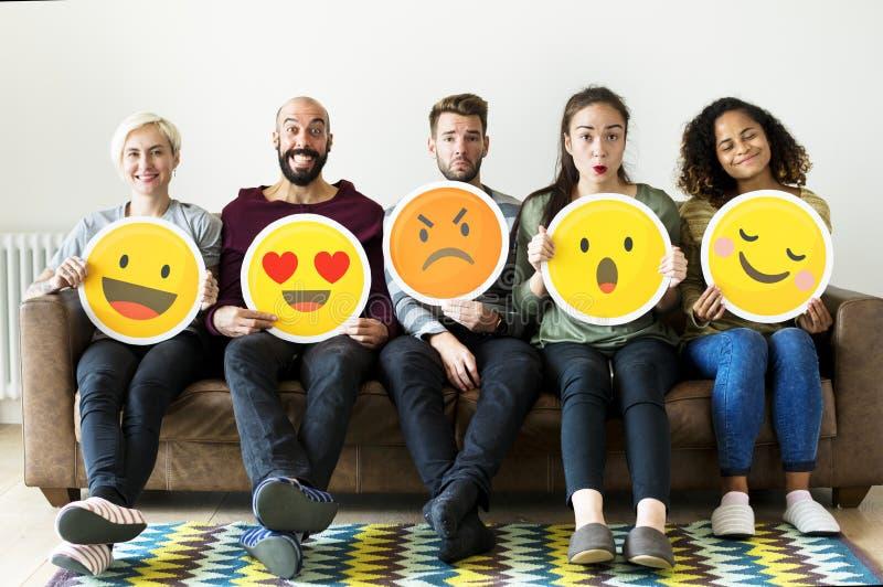 Grupp av hållande emoticonsymboler för olikt folk royaltyfria foton