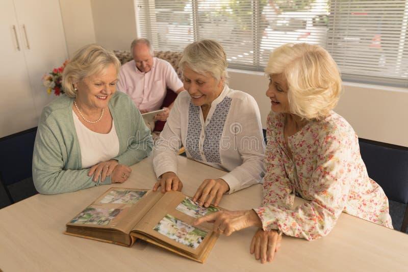 Grupp av höga kvinnor som ser fotoalbumet på vårdhemmet royaltyfri fotografi