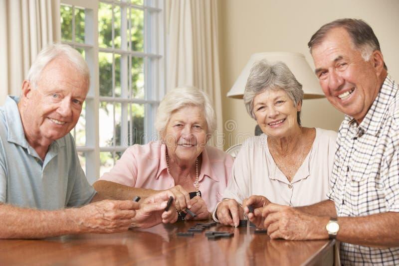 Grupp av höga par som hemma tycker om leken av domino fotografering för bildbyråer