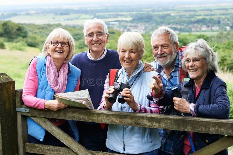 Grupp av höga vänner som fotvandrar i bygd arkivfoton