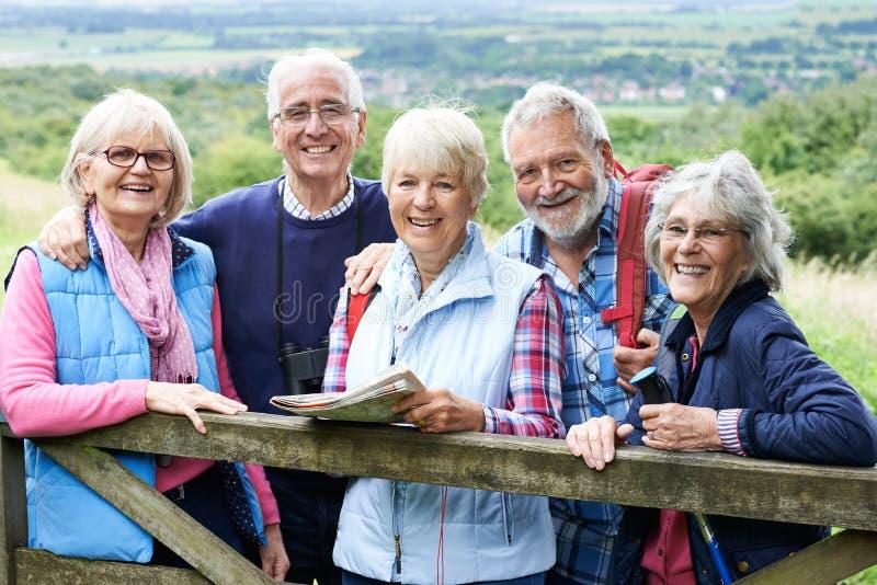 Grupp av höga vänner som fotvandrar i bygd royaltyfria bilder
