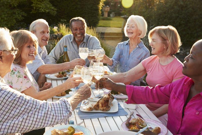 Grupp av höga vänner som gör ett rostat bröd på det utomhus- matställepartiet royaltyfri fotografi