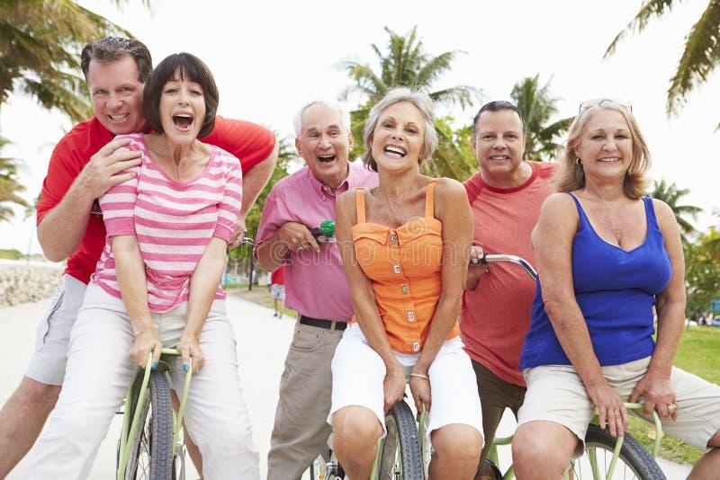 Grupp av höga vänner som har gyckel på cykelritt royaltyfria foton
