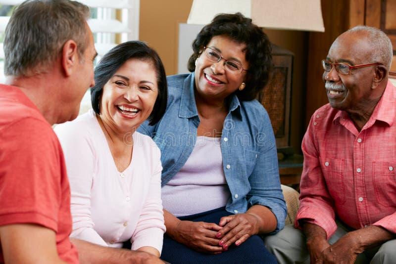Grupp av höga vänner som hemma pratar tillsammans royaltyfri foto