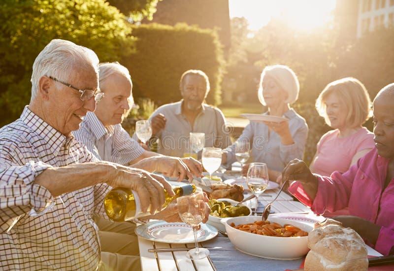 Grupp av höga vänner som hemma tycker om det utomhus- matställepartiet royaltyfria bilder