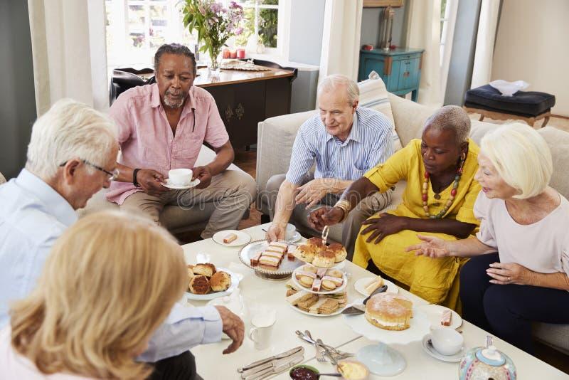 Grupp av höga vänner som hemma tycker om eftermiddagte tillsammans arkivfoton