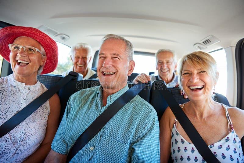 Grupp av höga vänner som sitter i baksida av Van Being Driven To Vacation royaltyfria bilder