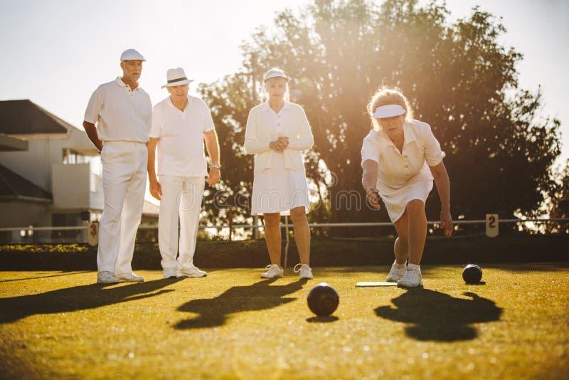 Grupp av höga vänner som spelar boules arkivbilder