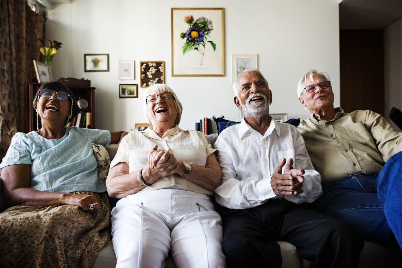 Grupp av höga vänner som tillsammans sitter och håller ögonen på tv royaltyfri foto