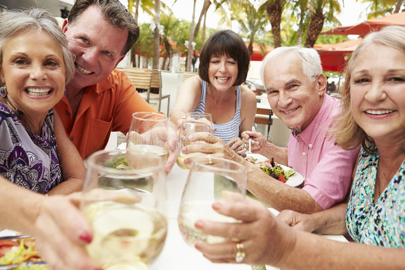 Grupp av höga vänner som tycker om mål i utomhus- restaurang royaltyfri fotografi