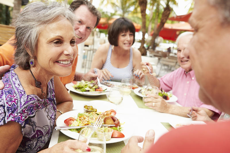 Grupp av höga vänner som tycker om mål i utomhus- restaurang royaltyfri bild