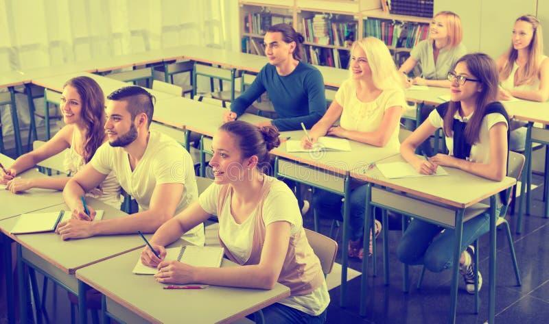 Grupp av högskolestudenter i klassrum arkivbild