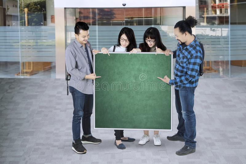 Grupp av högskolestudenter som pekar på grönt bräde med kopieringsutrymme arkivfoton