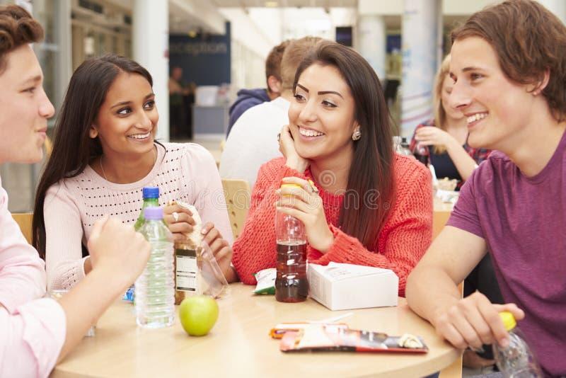 Grupp av högskolestudenter som tillsammans äter lunch royaltyfria bilder