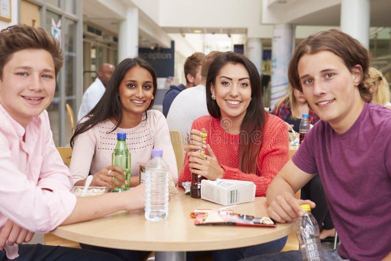 Grupp av högskolestudenter som tillsammans äter lunch royaltyfri bild