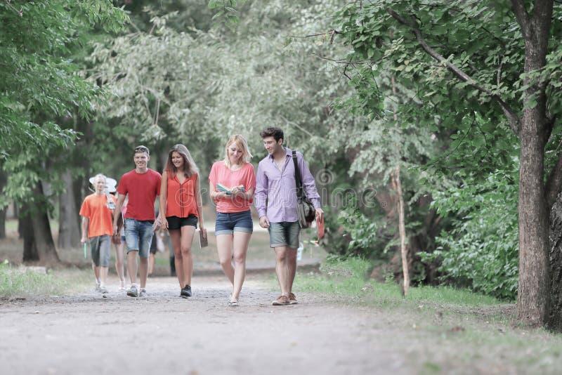 Grupp av högskolestudenter som tillsammans går i parkera arkivfoto