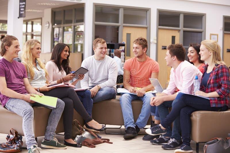 Grupp av högskolestudenter som tillsammans sitter och talar arkivfoton