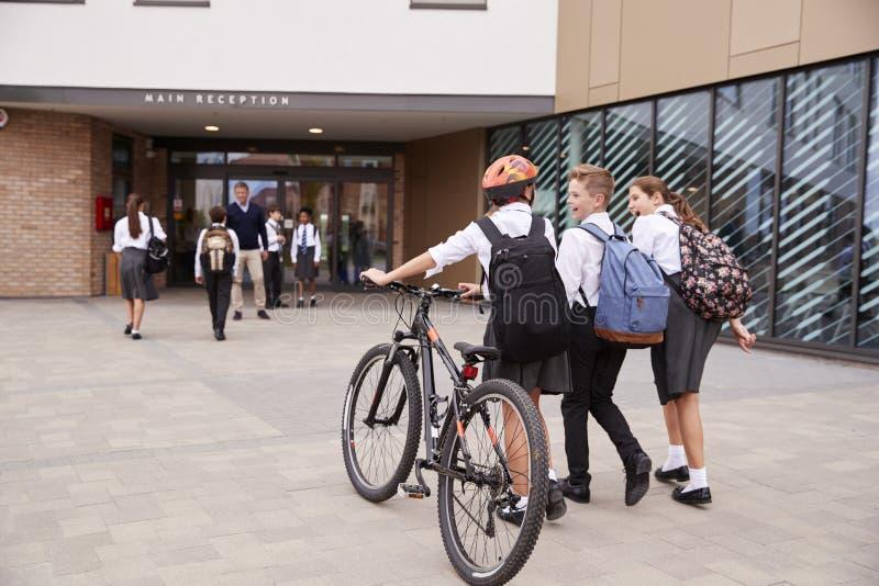 Grupp av högstadiumstudenter som bär enhetligt ankomma på skola som går eller rider cyklar som hälsas av läraren fotografering för bildbyråer