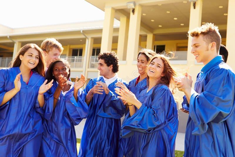Grupp av högstadiumstudenter som firar avläggande av examen royaltyfria foton