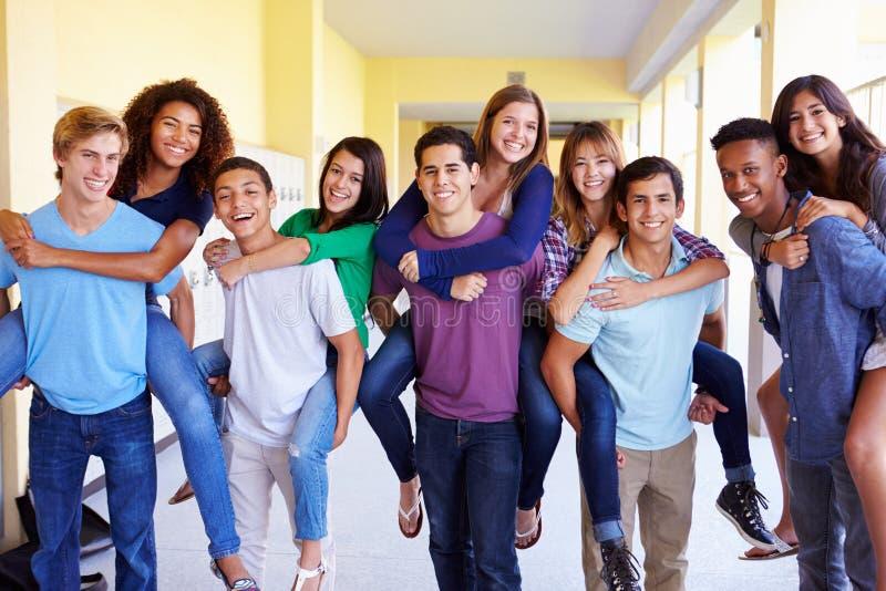 Grupp av högstadiumstudenter som ger ridturer på axlarna i korridor royaltyfria foton