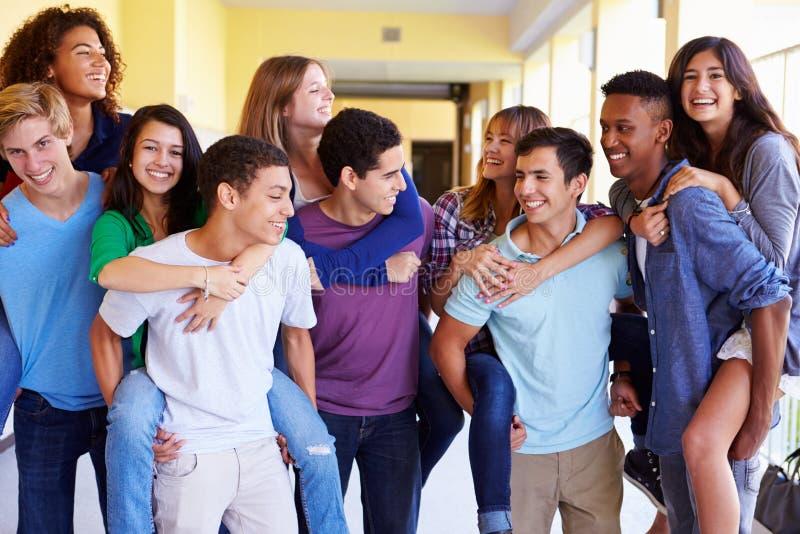 Grupp av högstadiumstudenter som ger ridturer på axlarna i korridor fotografering för bildbyråer