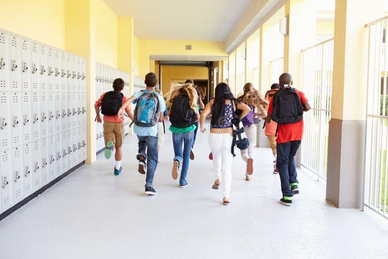 Grupp av högstadiumstudenter som kör längs korridoren royaltyfri foto