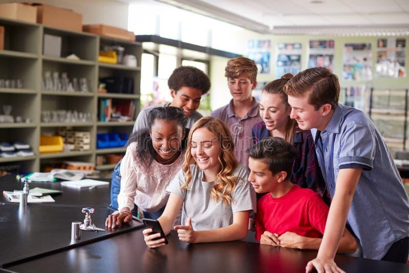 Grupp av högstadiumstudenter som ser meddelandet på mobiltelefonen i klassrum arkivbild