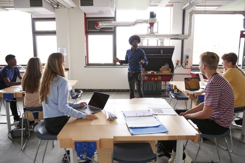 Grupp av högstadiumstudenter som sitter på arbetsbänkar som lyssnar till kursen för lärareIn Design And teknologi royaltyfria foton