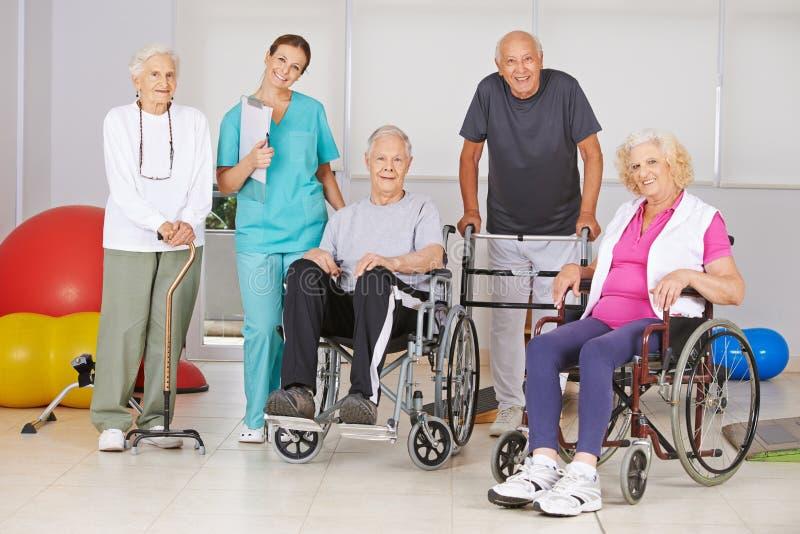 Grupp av högt folk på sjukgymnastik i vårdhem arkivfoto