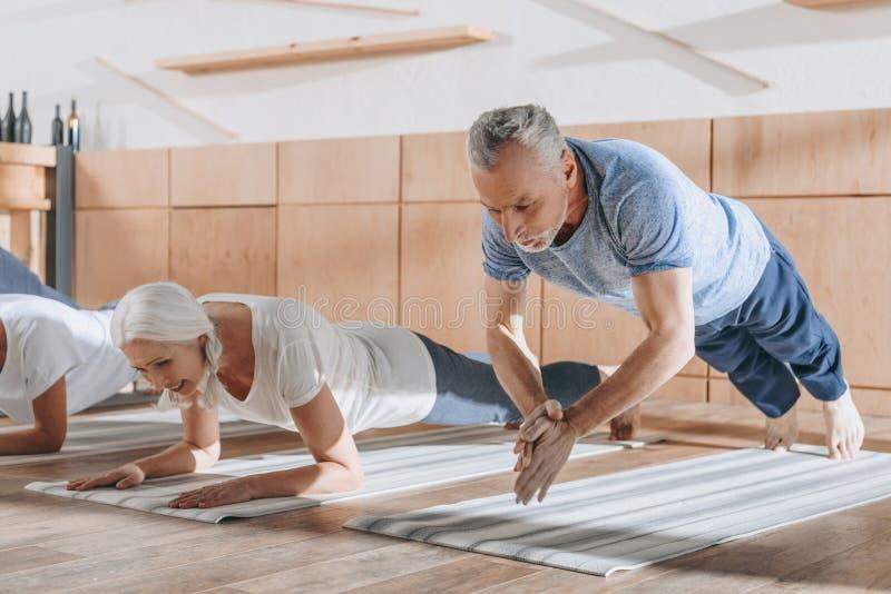 grupp av högt folk som gör plankan på yogamats arkivbilder