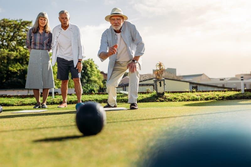 Grupp av högt folk som spelar boules i en gräsmatta royaltyfria bilder