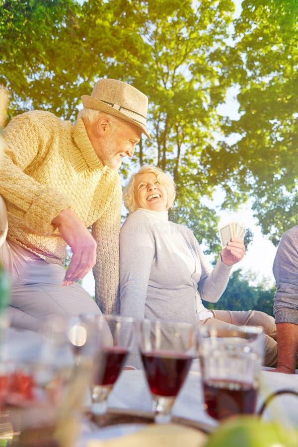Grupp av högt folk som spelar kort i sommar royaltyfria foton