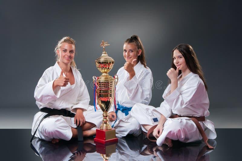 Grupp av h?rliga kvinnliga karatespelare som poserar med koppen p? den gr?a bakgrunden Fira det 1st st?llet arkivfoton