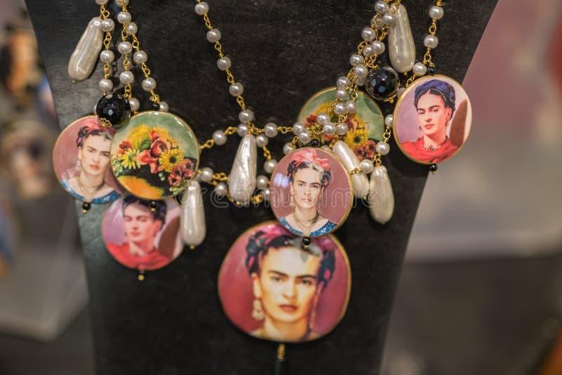 Grupp av halsband med färgade pärlor och Frida Kahlo Effigy som hänger på en skärmenhet royaltyfri fotografi
