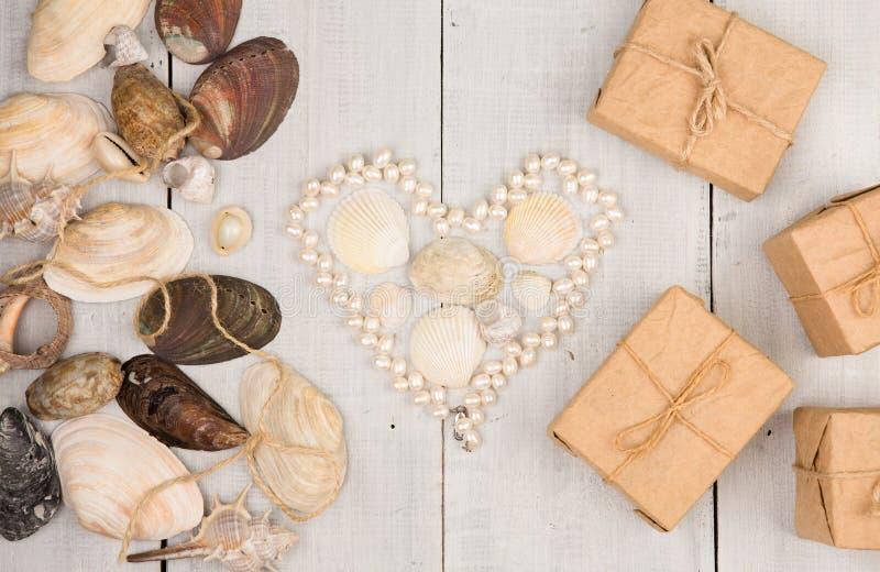 grupp av havsskal, pärlor som läggas ut i formen av hjärta, och gåvaaskar på vit träbakgrund royaltyfria foton
