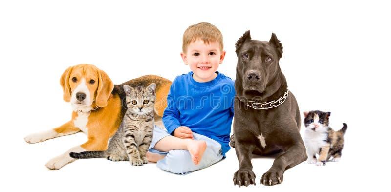 Grupp av husdjur och det lyckliga barnet som tillsammans sitter royaltyfri foto