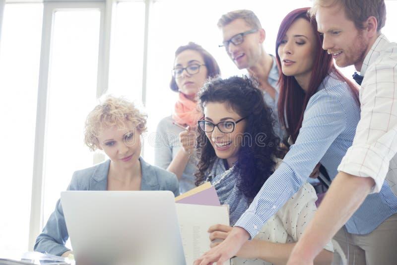 Grupp av idérika businesspeople som i regeringsställning använder bärbara datorn royaltyfri foto